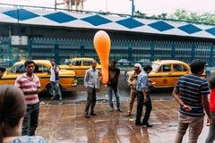 Povos indianos que esperam na frente do museu indiano vender o balão alaranjado do formulário longo com os táxis amarelos na estr imagens de stock royalty free