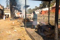 Povos locais durante a cerimônia da cremação ao longo do rio santamente de Bagmati em Bhasmeshvar Ghat no templo de Pashupatinath Imagem de Stock Royalty Free