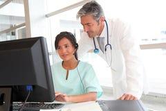 Povos médicos na frente do computador imagem de stock royalty free