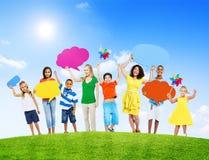 Povos misturados da idade que guardam bolhas coloridas do discurso fotografia de stock