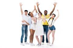 povos multi-étnicos novos felizes que levantam as mãos e que sorriem na câmera foto de stock