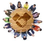 Povos multi-étnicos que guardam as mãos com símbolo do aperto de mão Foto de Stock Royalty Free