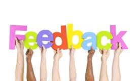 Povos multi-étnicos que guardam o feedback da palavra Imagem de Stock