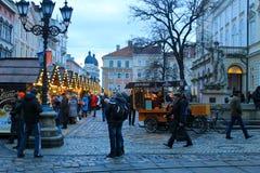 Povos não identificados que andam ao longo do Natal favoravelmente na noite Imagem de Stock Royalty Free