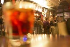 Povos na barra do mergulho com um cocktail de manhattan no primeiro plano Foto de Stock Royalty Free