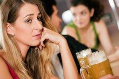 Povos na barra, mulher que é abandonada e triste Foto de Stock