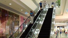 Povos na escada rolante no centro de comércio filme