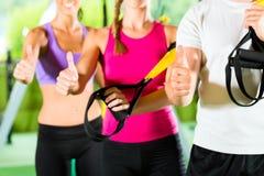 Povos na ginástica do esporte no instrutor da suspensão Fotografia de Stock