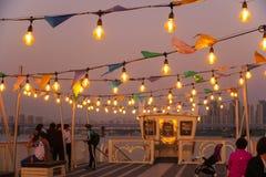 Povos na navigação do navio de cruzeiros ao longo do rio na noite Tiro Defocused imagens de stock royalty free