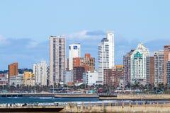 Povos na praia do amanhecer contra a skyline da cidade Imagens de Stock Royalty Free