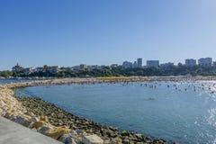 Povos na praia, no banho de sol e na natação, apreciando em férias fotografia de stock