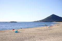Povos na praia no dia de mola imagem de stock