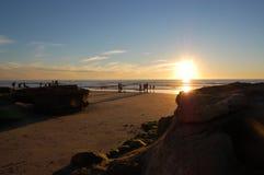 Povos na praia no por do sol fotos de stock
