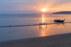 Povos na praia no por do sol em Tailândia, grupo novo do turista que anda no mar na noite Fotos de Stock