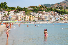 Povos na praia perto da margem de Giardini Naxos Fotos de Stock Royalty Free