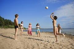 Povos na praia que joga o voleibol imagem de stock