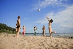 Povos na praia que joga o voleibol imagens de stock