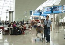 Povos na sala de estar de espera do terminal de aeroporto de Dubai Imagens de Stock