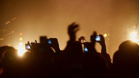 Povos nas mãos do aplauso do concerto contra as luzes do efeito estroboscópico, gravando com smartphones filme