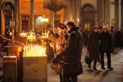 Povos nas velas da igreja e da luz Fotos de Stock Royalty Free
