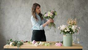 Povos, negócio, venda e conceito floristry - mulher de sorriso feliz do florista que faz o grupo no florista, ramalhete com video estoque