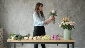 Povos, negócio, venda e conceito floristry - mulher de sorriso feliz do florista que faz o grupo no florista, ramalhete com filme