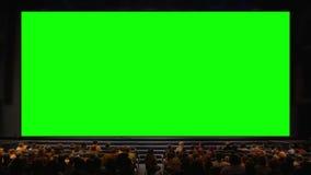 Povos no auditório com a tela da chave do croma video estoque