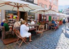 Povos no café da rua do terraço na cidade velha de Riga imagem de stock