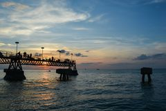 Povos no cais da pesca no por do sol Fotografia de Stock