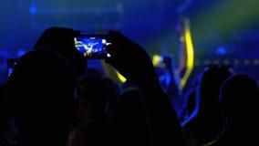 Povos no concerto de rocha da música que toma fotos ou que grava o vídeo com Smartphones video estoque