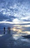 Povos no crepúsculo sobre os planos bolivianos de sal fotografia de stock