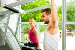 Povos no gym do esporte na máquina da aptidão Foto de Stock