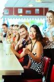 Povos no jantar americano ou restaurante com agitações de leite Imagens de Stock