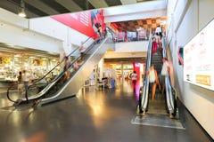 Povos no movimento nas escadas rolantes na alameda de compra moderna Imagem de Stock Royalty Free