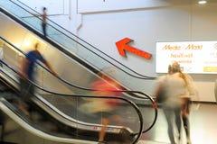 Povos no movimento nas escadas rolantes na alameda de compra moderna Foto de Stock Royalty Free