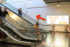Povos no movimento nas escadas rolantes na alameda de compra moderna Imagem de Stock