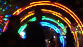 Povos no parque de diversões na noite, luz colorida de atrações modernas como o fundo video estoque