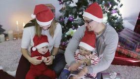Povos novos da família de quatro pessoas que comemoram o ano novo perto da árvore de Natal vídeos de arquivo