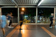 Povos obscuros do viajante que andam na cena da noite da ponte fotografia de stock