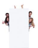 Povos ocasionais atrás de uma bandeira grande que faz o sinal aprovado Fotografia de Stock