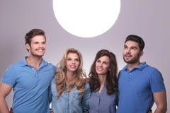 Povos ocasionais que olham acima em uma bola grande da luz Fotografia de Stock Royalty Free