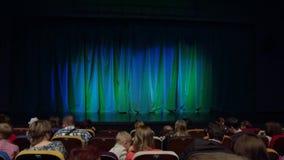 Povos, pais, crianças no auditório antes da mostra Cortina azul esverdeado Uma produção teatral video estoque