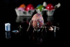 Povos pequenos com um ovo gigante Fotos de Stock Royalty Free