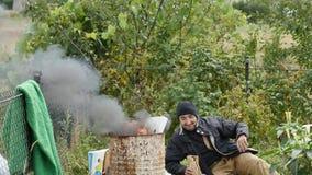 Povos pobres que aquecem-se perto do tambor de lixo do fogo e da vodca da bebida video estoque