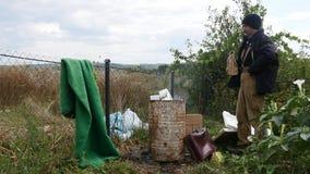 Povos pobres que aquecem-se perto do tambor de lixo do fogo e da vodca da bebida filme
