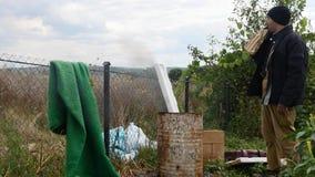 Povos pobres que aquecem-se perto do tambor de lixo do fogo e da vodca da bebida vídeos de arquivo