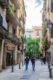 Povos que andam abaixo da rua estreita entre lojas/lojas em Barcelona imagens de stock royalty free