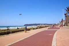 Povos que andam ao longo do passeio pavimentado na parte dianteira da praia Fotografia de Stock Royalty Free