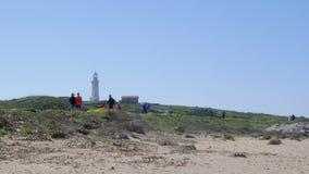 Povos que andam ao longo do trajeto da praia perto do mar com o farol no fundo em Paphos, Chipre filme