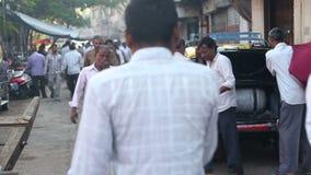 Povos que andam através de uma rua movimentada em Mumbai filme